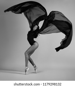 A ballerina posing with a black cloth like a bird. Black and white photo.