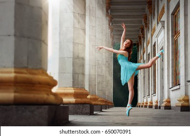 Ballerina posing out of doors. Ballerina dance in a blue dress on a background of white columns