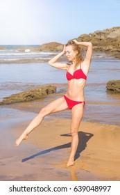 Ballerina in red bikini practice dancing at the seashore