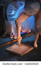 The ballerina rubs the toe of pointe shoes in a box with pounded rosin to prevent slipping