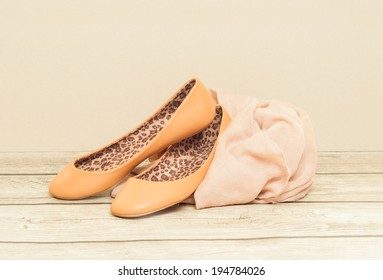 Ballerina shoes and scarf on wooden board