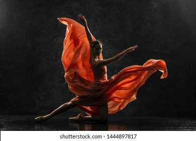 Ballerina. Silhouette photo of a young  ballet dancer dressed in a long peach dress, pointe shoes with ribbons. The girl performs an graceful dance movement. Beautiful classic ballet. Ballet studios.