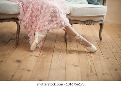 Ballerina sits, legs in pointe shoes close-up