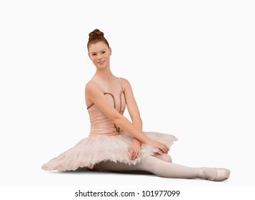 Ballerina sitting against a white background