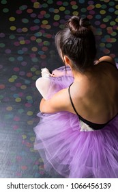 ballerina sitting in confetti in purple tutu