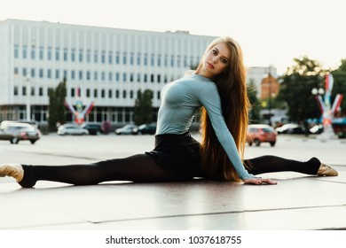 Ballerina sitting in gymnastic split pose in middle of city street. buildings background. beautiful female model stretching, twine outdoor, long hair.