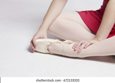 Ballerina sitting on a white floor, touching her foot, suffering pain on her fingers and ankle. No pain no gain.