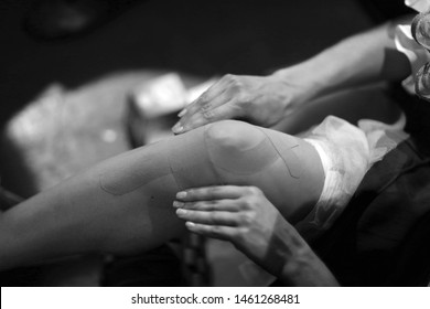 Ballerina sticks kinesio tape on the knee and lower leg before the performance