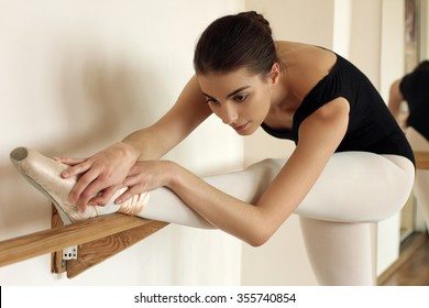 Ballerina stretches herself near barre and wall in the classroom
