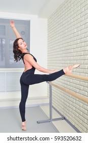 Ballerina stretches herself near barre in the classroom, beautiful women weared in black bodysuit practicing ballet