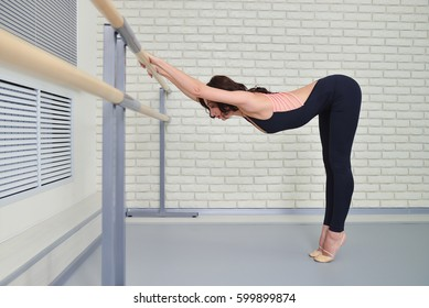 Ballerina stretches herself near barre in the classroom, beautiful women stretching