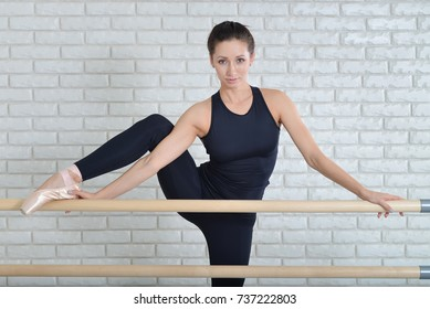 Ballerina stretches herself near barre at ballet studio, close up portrait of beautiful woman dancer looking at camera.