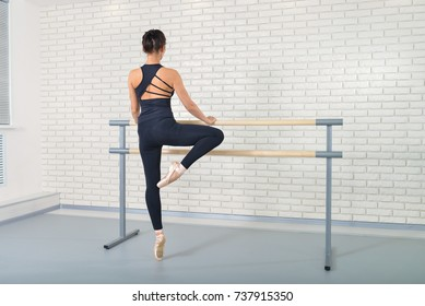 Ballerina stretches herself near barre at ballet studio, full length portrait, shoot from behind.