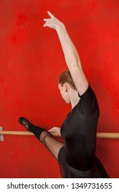 Ballerina Stretching At Barre In Training Studio