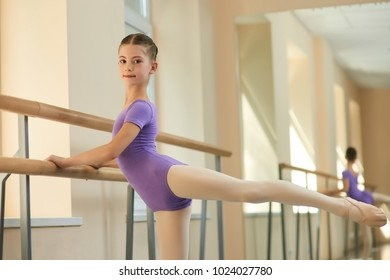 Ballerina stretching out and looking at camera. Young beautiful girl is training stretch of her leg on barre and smiling. Young ballet-dancer in leotard workout.