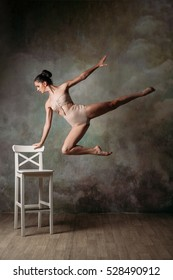ballerina in a studio in a jump over a chair