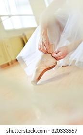 ballerina ties a pointe shoe