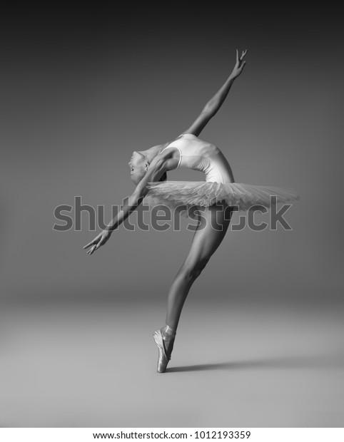 Балерина в туту и пуант обувь делает красивую позу.  Черно-белая фотография.