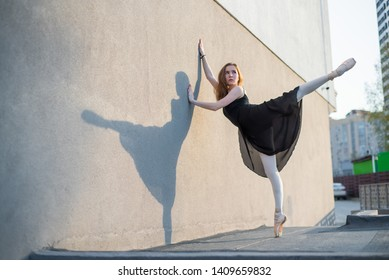 Ballerina in tutu posing standing near the wall. Beautiful young woman in black dress and pointe dancing outside. Gorgeous ballerina performing a dance outdoors