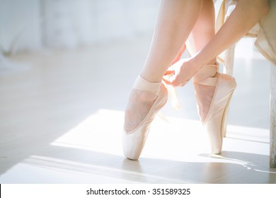 Ballerina tying pointe ballet shoes