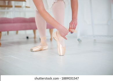 ballerina wears and ties ballet flats before ballet dance show, professional costume, the beauty of classical ballet.