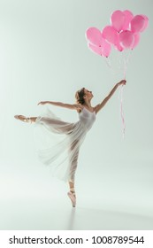 ballerina in white dress dancing with pink balloons, isolated on white