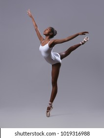 "A ballerina in a white leotard makes a pose ""Swallow"""