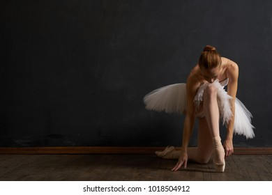 ballerina in a white pack and pointe shoes on a dark background