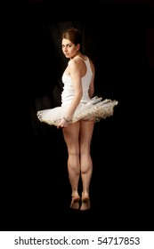Ballerina in white tutu on black