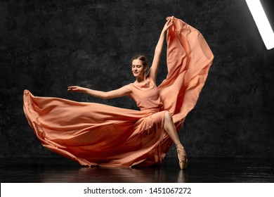 Ballerina. A young ballet dancer dressed in a long peach dress, pointe shoes with ribbons. The girl performs an elegant, graceful dance movement. Beautiful classic ballet. Advertising ballet studio.