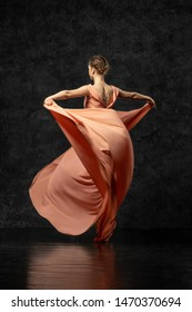 Ballerina. A young dancer dressed in a long peach dress, pointe shoes with ribbons. Performs a graceful, graceful dance movement  which is visible from the back. Beautiful classic ballet.