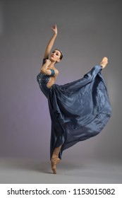 Ballerina. A young graceful ballerina dressed in professional attire, shoes and a blue weightless dress demonstrates dance skills. The beauty of classical ballet.