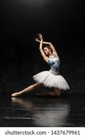 Ballerina. A young graceful ballerina dressed in professional attire, pointe shoes with ribbons and a white tutu, demonstrates dance skills. Beautiful classic ballet.