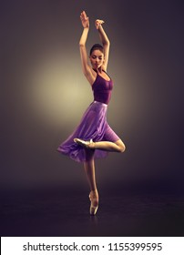 Ballerina. Young graceful woman ballet dancer, dressed in professional outfit, shoes and violet  weightless skirt is demonstrating dancing skill. Beauty of classic ballet.