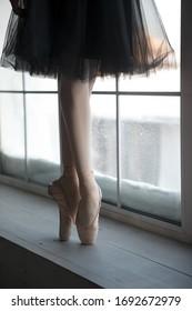 ballerina's feet on point in black tutu over white window