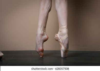 Ballerina's feet on the point  brown backgroung