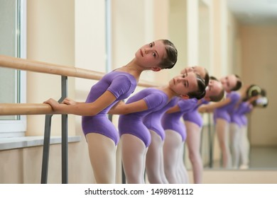 Ballerinas perform exercises on a ballet barre. Cute teen ballerinas doing different exercises using choreographic equipment. Stretching exercises by ballet girls.