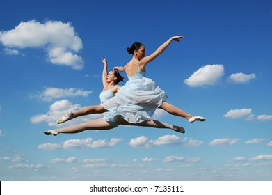 Ballerinas performing outdoors against a blue sky