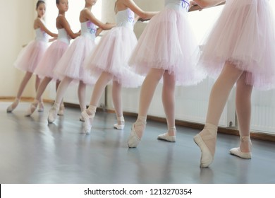 Ballerinas training at hall. Legs of young ballet dancers having practice near ballet barre