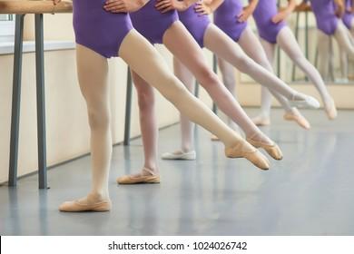 Ballet background, ballerinas having practice. Legs of young dancers ballerinas in class of classical dance. Start lesson of ballet dance for teens.
