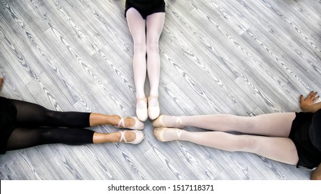 Ballet background. Little ballerinas legs in pointe shoes on floor, top view