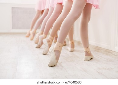 Ballet background, young ballerinas training. Little dancers legs in pointe shoes, making exercises. Classical dance school, copy space