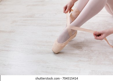 Ballet backgroung with copy space. Choreography and dancing classes concept. Beautiful legs of young ballerina putting on pointe shoes at white wooden floor background