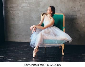 Ballet dancer ballerina in beautiful light blue dress tutu skirt posing sitting on vinage chair in loft studio
