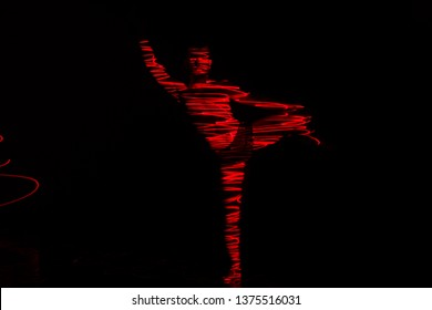 Ballet dancer dancing in front of and red light while expressing the hell with his magnificent dance moves, long exposure motion blur