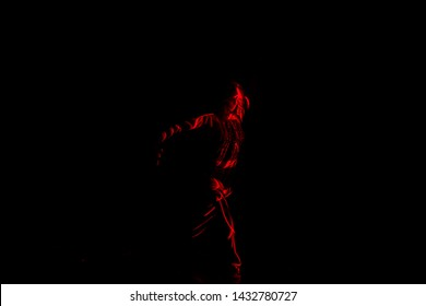 Ballet dancer dancing in front of and red light while expressing the hell with her magnificent dance moves, long exposure motion blur