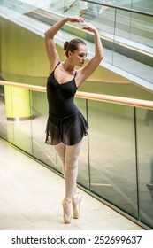 Ballet dancer dancing in modern business premises at escalator