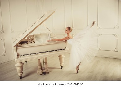 Ballet dancer is dancing in the white hall. In this room piano is standing