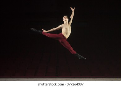 Ballet dancer jumping high, in air. At theater on a stage.