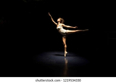 Ballet dancer in pointe shoes in an arabesque. Studio low key lighting with one spot light.
